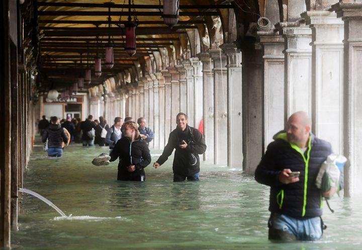 Des touristes sous une arche inondée à Venise en Italie, le 29 octobre 2018. (MIGUEL MEDINA / AFP)