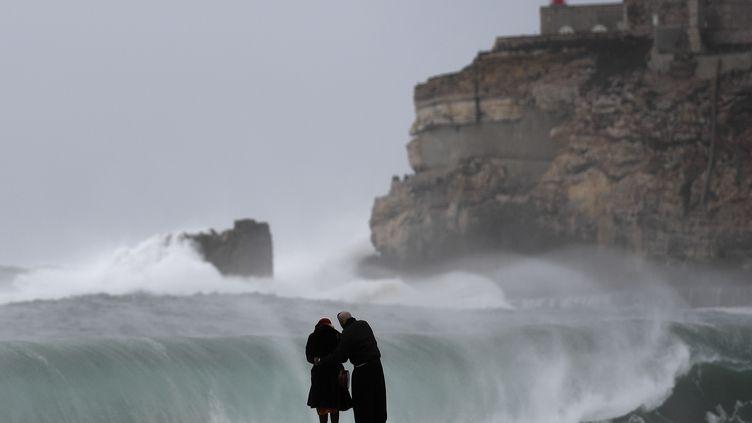 Un couple observe des vagues déferler sur une plage de Nazare, au Portugal (illustration). (FRANCISCO LEONG / AFP)