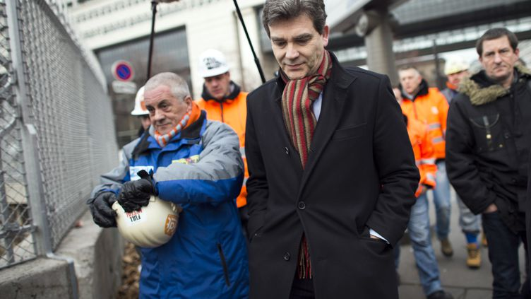 Le ministre du Redressement productif, Arnaud Montebourg, le 30 novembre 2012, à Paris, avec des employés d'ArcellorMittal. (FRED DUFOUR / AFP)