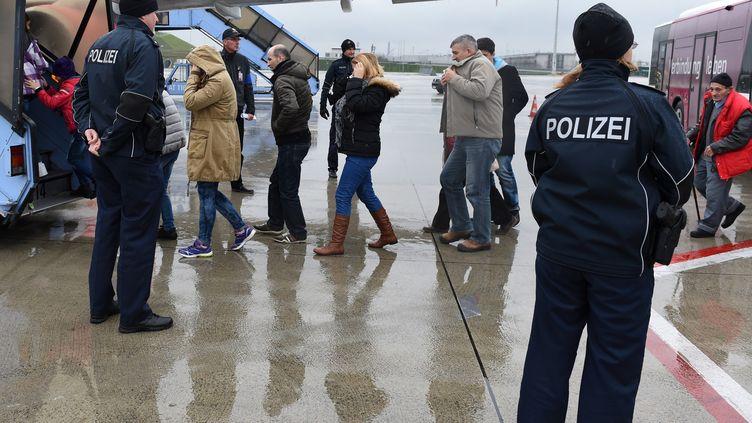 Des policiers escortent des migrants dans un avion en vue de leur expulsion, le 9 décembre 2015 à l'aéroport de Munich (Allemagne). (CHRISTOF STACHE / AFP)