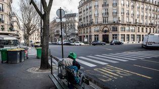 Une personne sans domicile regarde, assise sur un banc, une rue parisienne vide, lors de l'épidémie du coronavirus covid-19, le 17 mars 2020. (MARTIN BUREAU / AFP)