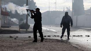 Des policiers tunisiens tirent des grenades lacrymogènes sur les manifestants lors d'une manifestation le 25 décembre 2018 dans la ville de Kasserine, après l'enterrement du journaliste qui s'est immolé par le feu. (HATEM SALHI / AFP)