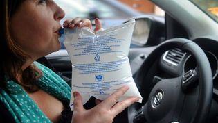 Une femme souffle dans un ethylotest à Quimper (Finistère), le 1er juillet 2012. (FRED TANNEAU / AFP)