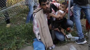 Des migrants tentent de franchir la frontière entre la Serbie et la Hongrie, près de Horgos, le 14 septembre 2015, après la mise en place de barbelés par les autorités hongroises. (MARKO DJURICA / REUTERS)