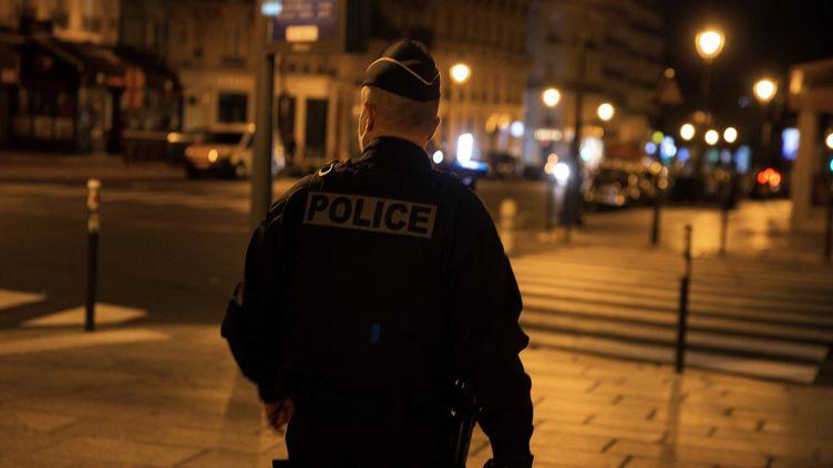 Un policier patrouille, le 17 octobre 2020 à Paris, au début d'un couvre-feu mis en place pour lutter contre la propagation du Covid-19. (ABDULMONAM EASSA / AFP)
