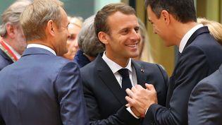 Emmanuel Macron au milieu duprésident du Conseil européenDonald Tusk (à gauche) et du Premier ministre espagnol Pedro Sanchez, lors d'un sommet européen à Bruxelles le 28 juin 2018. (DURSUN AYDEMIR / ANADOLU AGENCY / AFP)