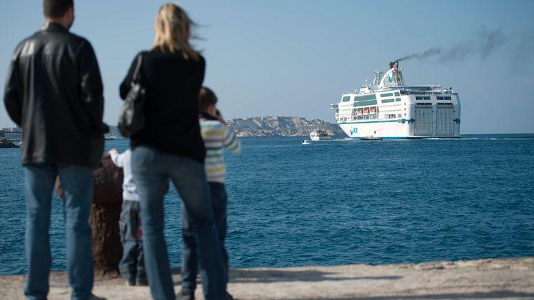 Des passants regardent un navire de la SNCM, le 28 octobre 2014 à Marseille (Bouches-du-Rhône). (BERTRAND LANGLOIS / AFP)