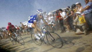 Le coureur belge Tom Boonen (en bleu) se fraie un chemin dans la poussière des pavés de Paris-Roubaix, le 15 avril 2007. (FRANCK FIFE / AFP)