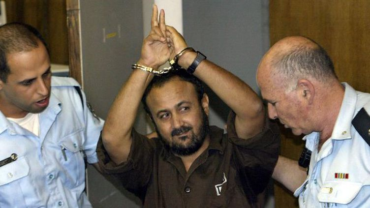Marwan Barghouti, poignets menottés, fait le «V» de la victoire en allant au tribunal de Tel Aviv où se tenait son procès, le 20 mai 2004.  (David Siverman /  AFP)