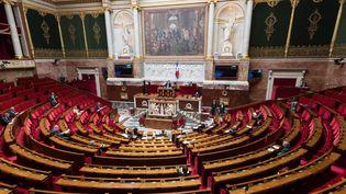 Des députés en nombre très réduit, à cause des règles de distanciation sociale, siègent dans l'hémicycle de l'Assemblée nationale lors des questions au gouvernement, le 21 avril 2020. (JACQUES WITT / AFP)