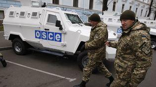 Des soldats ukrainiens passent devant des véhicules blindés de la mission de l'OSCE en Ukraine, le 12 novembre 2014, à Kiev. (VLADIMIR SHTANKO / ANADOLU AGENCY / AFP)