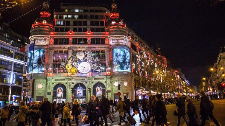 Des passants marchent devant le magasin Printemps illuminé pour les fêtes de fin d'années, à Paris, le 22 décembre 2015. (IRINA KALASHNIKOVA / RIA NOVOSTI/ AFP)