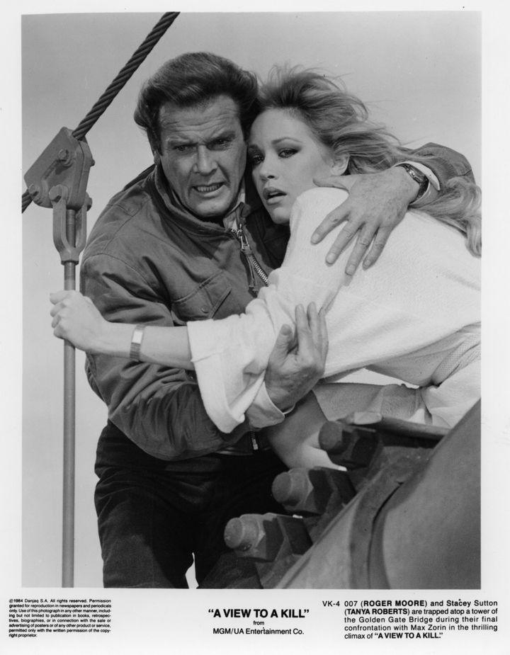 """L'acteur Roger Moore aux côtés de Tanya Roberts dans """"Dangereusement vôtre"""" (1987) (HULTON ARCHIVE / MOVIEPIX)"""