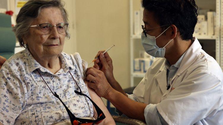 Une patiente âgée reçoit sa dose de rappel de vaccin contre le Covid-19, à Paris, le 13 septembre 2021. (THOMAS COEX / AFP)