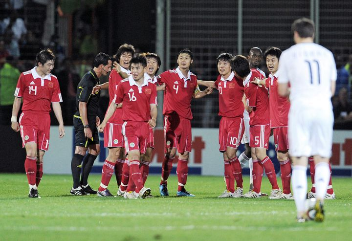 Les joueurs chinois célèbrent leur ouverture du score face à un André-Pierre Gignac dépité, le 4 juin 2010, à Saint-Pierre de la Réunion. (FRANCK FIFE / AFP)