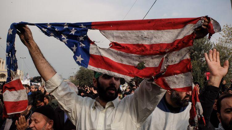 Un manifestant brandit le drapeau américain brûlé lors d'une manifestation anti-américaine à Téhéran le 3 janvier 2020. (ROUZBEH FOULADI / MAXPPP)