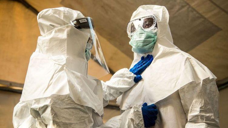 Chaque professionnel de santé vérifie le bon état des combinaisons de protection de ses collègues. (SUMY SADURNI/ AFP VIA GETTY IMAGES)