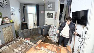 Une habitante examine les dégâts subis par une maison dans une zone détruite par les récentes inondations, à Trooz (Belgique), le 16 juillet 2021. (ERIC LALMAND / BELGA / AFP)