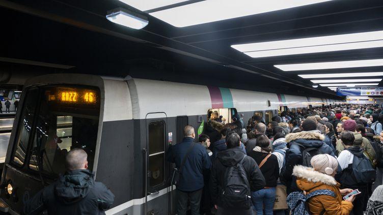 Des passagers tentent de rentrer dans une rame du RER B pendant la grève contre la réforme des retraites, le 13 décembre 2019, à Paris. (GREG LOOPING / HANS LUCAS / AFP)