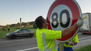 Des employés de DIR Est installent un panneau de limitation de vitesse à 80 km/h sur un route nationale à Hyet (Haute-Saône), le 1er juillet 2015. (SEBASTIEN BOZON / AFP)