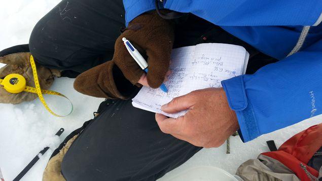 (L'ingénieur Christian Vincent note sur son carnet des données des carottes © Guillaume Battin)