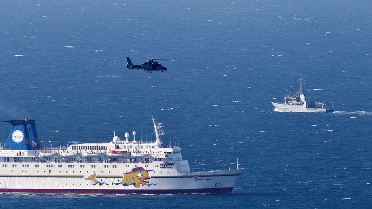 Un navire militaire israélien (D) et un hélicoptère de l'armée israélienne à la recherche des débris du drone abattu au large de Haïfa (Israël), le 25 avril 2013. (JACK GUEZ / AFP)
