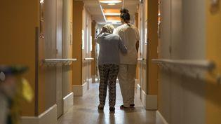 Une soignante aide une pensionnaire d'un Ehpad du Doux à traverser le couloir, 16 avril 2020 (photo d'illustration). (SEBASTIEN BOZON / AFP)