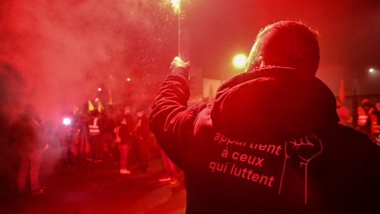Un employé de Bridgestone tient une fusée éclairante devant l'usine de Béthune(Pas-de-Calais), le 27 novembre 2020. (DENIS CHARLET / AFP)