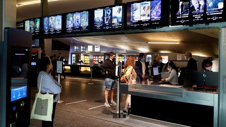 Des spectateurs réservent leur place de cinéma le 29 avril, à l'annonce de la réouverture des salles, prévue le 19 mai 2021, par Emmanuel Macron. (THOMAS COEX / AFP)