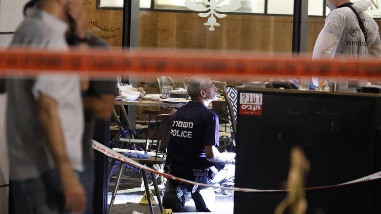 Des policiers examinent le restaurant de Tel Aviv (Israël) où une fusillade a fait au moins quatre morts, mercredi 8 juin 2016. (JACK GUEZ / AFP)