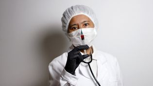 Image d'illustration d'unhomme masqué posant avec une seringue. (CHRISTOPH HARDT / GEISLER-FOTOPRES / AFP)