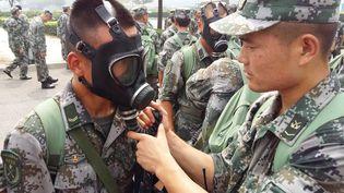 Des militaires chinois s'équipent de masques à gaz, le 15 août 2015 à Tianjin (Chine). (XU ZHUANGZHI / XINHUA)