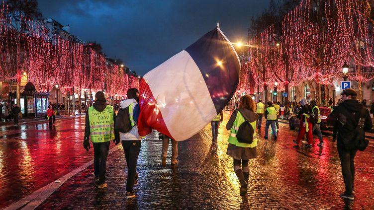 """Des """"gilets jaunes"""" se sont donné rendez-vous sur les Champs-Élysées pour le Nouvel An. (ZAKARIA ABDELKAFI / AFP)"""