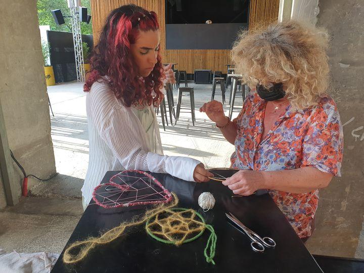 Gabrielle, organisatrice de l'atelier, et Isabelle, participante, s'affairent à la fabrication d'un attrape-rêve. Paris, le 11 août 2021 (LEELA BADRINATH)
