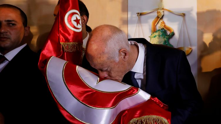 Kaïs Saïed embrasse le drapeau de son pays à Tunis juste après l'annonce de son élection à la présidence tunisienne le 13 octobre 2019. (REUTERS - ZOUBEIR SOUISSI / X02856)