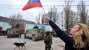 Une Ukrainienne agite un drapeau russe en signe de soutien devant un militaire, àBalaklava, une petite ville située près de Sébastopol (Ukraine), le 1er mars 2014. (VIKTOR DRACHEV / AFP)
