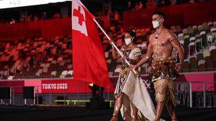 La délégation des îles Tonga,lors de la parade des nations, à la cérémonie d'ouverture des Jeux olympiques de Tokyo, au Stade olympique de Tokyo (Japon), le 23 juillet 2021. (HANNAH MCKAY / POOL / AFP)