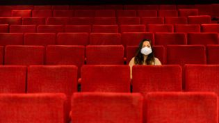 Une spectarice masquée dans une salle de théâtre vide. (ST?PHANE FERRER YULIANTI / HANS LUCAS)