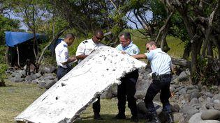 Des gendarmes manipulent un débris d'avion,sur le littoral de Saint-André de La Réunion. (MAXPPP)