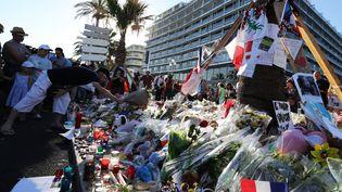 Des passants déposent des bouquets de fleurs, des bougies et des messages, le 16 juillet 2016, sur le mémorial improvisé en hommage aux victimes de l'attentat au camion perpétré sur la promenade des Anglais à Nice lors du 14-Juillet. (VALERY HACHE / AFP)