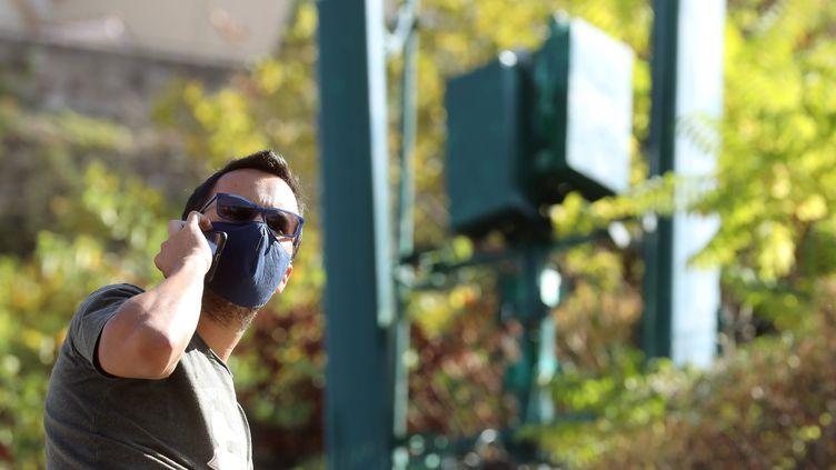Un homme au téléphone à côté d'une antenne 5G. Photo d'illustration. (JEAN FRAN?OIS OTTONELLO / MAXPPP)