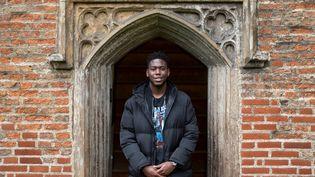 L'étudiant Matthew Omoefe Offeh pose devant le portail de l'université de Cambridge (octobre 2020). (JUSTIN TALLIS / AFP)