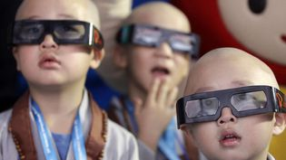 De jeunes garçons qui expérimentent la vie de moines bouddhistes durant une semaine, regardent un film en 3D lors de la visite d'un musée à Séoul (Corée du Sud), le 24 mai 2012. (LEE JIN-MAN / AP / SIPA)