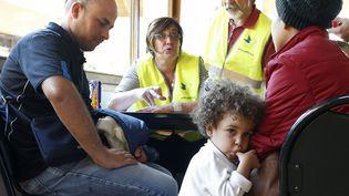 Des réfugiés irakiens et syriens sont enregistrés par des membres du Secours populaire à leur arrivée dans un centre de Cergy-Pontoise (Val-d'Oise), le 9 septembre 2015. ( JACKY NAEGELEN / REUTERS)