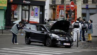 Des policiers examinent une voiture qui aurait pu avoir servi à la préparation des attentats de vendredi, mardi 17 novembre dans le 18e arrondissement de Paris. (KENZO TRIBOUILLARD / AFP)