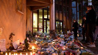 Des fleurs et des bougies déposées, le 17 octobre 2020, devant l'entrée du collège de Conflans-Sainte-Honorine (Yvelines), où enseignait Samuel Paty. (BERTRAND GUAY / AFP)
