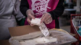 Des bénévoles des Restos du Cœur mettent dans des paquets destinés aux bénéficiaires des savons recyclés fabriqués à partir des savons usagés des hôtels, le 24 mars 2021 à Givors (Rhône). (JEFF PACHOUD / AFP)