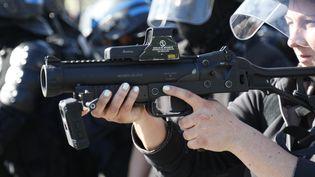 Une policière brandit un LBD lors de heurts place de la République à Paris, le 20 avril 2019. (ZAKARIA ABDELKAFI / AFP)