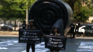 Des militants de Greenpeace protestent contre le projet de forage de Total au large de la Guyane et d'un récif corallien découvert dans l'embouchure de l'Amazone, le 28 septembre 2017, à Rio de Janeiro (Brésil). (PILAR OLIVARES / REUTERS)