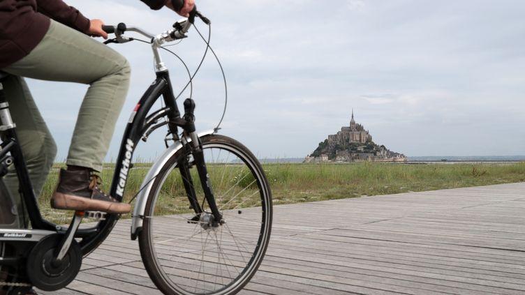 Un touriste à vélo près du Mont-Saint-Michel (Manche). (KENZO TRIBOUILLARD / AFP)